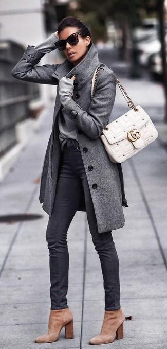 Come indossare: cappotto grigio, maglione con scollo a v grigio, jeans aderenti neri, stivaletti in pelle scamosciata marrone chiaro