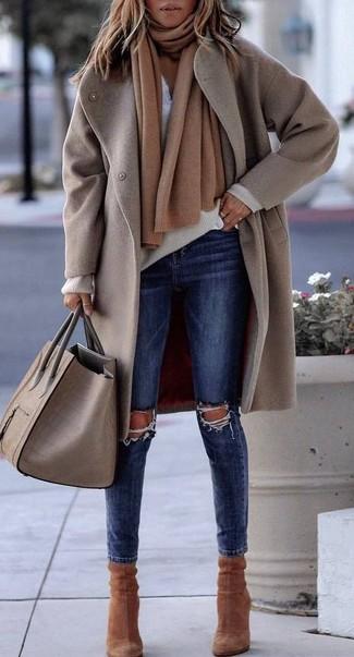 Come indossare e abbinare: cappotto beige, maglione con scollo a v beige, serafino bianco, jeans aderenti strappati blu scuro