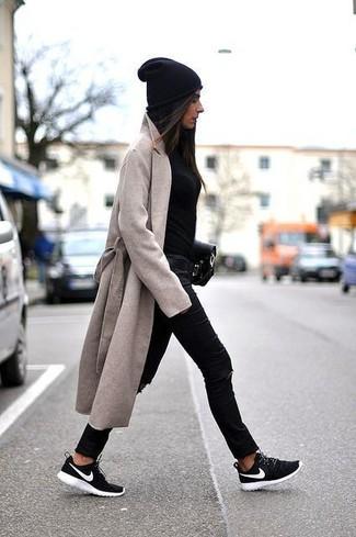 Come indossare: cappotto beige, maglione girocollo nero, jeans aderenti strappati neri, scarpe sportive nere e bianche
