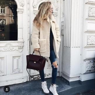 Come indossare e abbinare: cappotto di pile beige, maglione girocollo nero, jeans aderenti strappati blu scuro, stivali piatti stringati in pelle bianchi