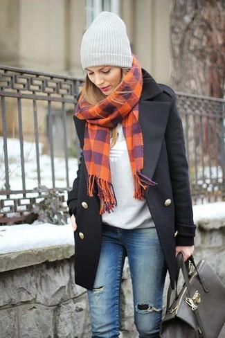 Sfrutta gli abiti più adatti al tempo libero con questa combinazione di un cappotto nero e jeans aderenti strappati blu.