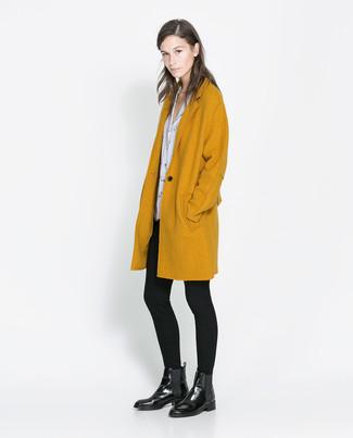 Come indossare e abbinare: cappotto senape, camicetta manica corta stampata bianca e nera, leggings neri, stivali chelsea in pelle neri