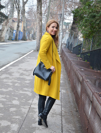 Come indossare: cappotto senape, stivali sopra il ginocchio in pelle neri, borsa a secchiello in pelle nera, orecchini blu