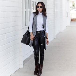 Come indossare e abbinare: cappotto senza maniche grigio, dolcevita bianco, jeans aderenti in pelle neri, stivaletti in pelle marrone scuro