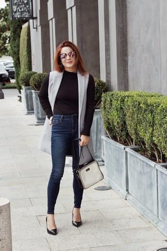 Come indossare: cappotto senza maniche grigio, maglione girocollo nero, jeans aderenti blu scuro, décolleté in pelle neri