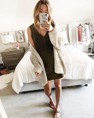 Come indossare: cardigan aperto lavorato a maglia beige, vestito a tubino in pelle scamosciata marrone scuro, infradito in pelle marroni, anello dorato
