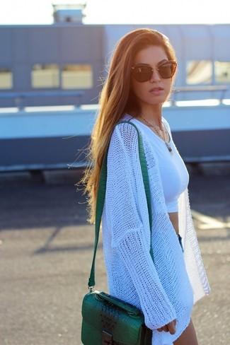 Come indossare: cardigan aperto lavorato a maglia bianco, top corto bianco, pantaloncini di jeans blu, borsa a tracolla in pelle verde