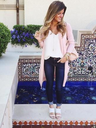 Come indossare e abbinare: cardigan aperto rosa, canotta di seta bianca, jeans aderenti blu scuro, sandali con tacco in pelle bianchi