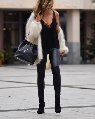 Come indossare e abbinare: cardigan aperto morbido bianco, canotta di seta nera, leggings in pelle neri, stivaletti in pelle scamosciata neri