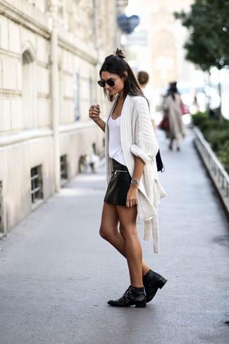 Come indossare e abbinare: cardigan aperto lavorato a maglia bianco, canotta bianca, minigonna in pelle nera, stivaletti in pelle con borchie neri