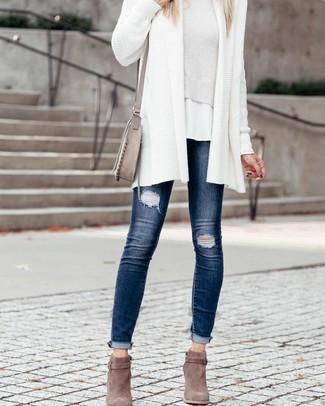 Come indossare: cardigan aperto lavorato a maglia bianco, maglione corto bianco, t-shirt girocollo bianca, jeans aderenti strappati blu scuro