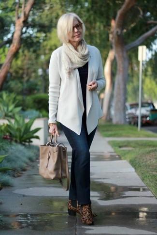 Come indossare: cardigan aperto bianco, maglione girocollo nero, jeans blu scuro, stivaletti in pelle scamosciata leopardati marroni