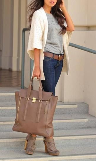 Come indossare: cardigan aperto lavorato a maglia bianco, t-shirt girocollo stampata grigia, jeans aderenti blu scuro, stivaletti in pelle marroni