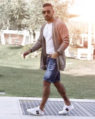 Come indossare e abbinare: cardigan aperto grigio, t-shirt girocollo bianca, pantaloncini di jeans strappati blu, sneakers basse stampate bianche