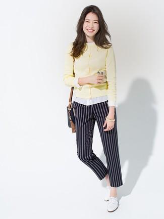 Come indossare e abbinare: cardigan giallo, blusa abbottonata bianca, pantaloni stretti in fondo a righe verticali blu scuro, scarpe oxford in pelle bianche