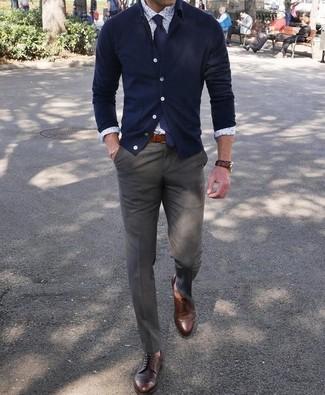 Come indossare e abbinare: cardigan blu scuro, camicia elegante stampata bianca, pantaloni eleganti verde oliva, scarpe derby in pelle marrone scuro