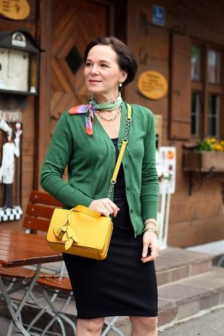 Moda donna anni 50: Mostra il tuo stile in un cardigan verde con una gonna a tubino nera per un elegante abbigliamento da ufficio.