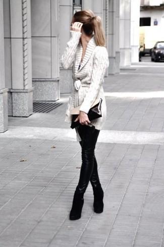 Come indossare: cardigan con collo a scialle beige, leggings in pelle neri, stivaletti con zeppa in pelle scamosciata neri, pochette in pelle nera e bianca