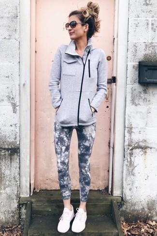 Come indossare e abbinare: cardigan con zip di pile grigio, leggings effetto tie-dye grigio scuro, scarpe sportive rosa, occhiali da sole marrone scuro