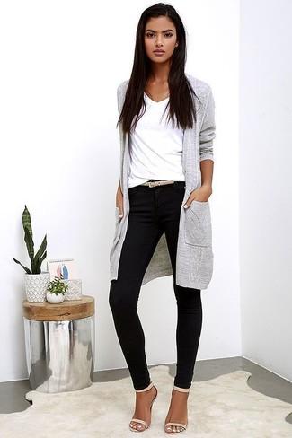 Come indossare: cardigan lungo grigio, t-shirt con scollo a v bianca, pantaloni skinny neri, sandali con tacco in pelle beige