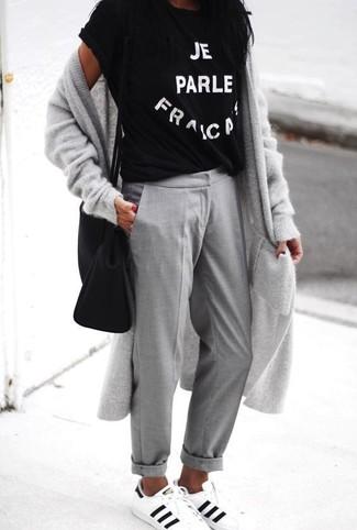 Come indossare: cardigan lungo grigio, t-shirt girocollo stampata nera e bianca, chino grigi, sneakers basse in pelle bianche e nere