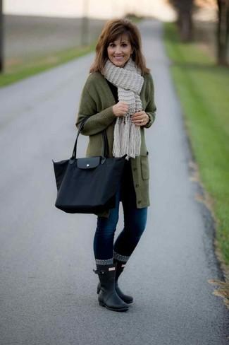 Come indossare e abbinare: cardigan lungo verde oliva, t-shirt manica lunga nera, jeans aderenti blu scuro, stivali di gomma neri