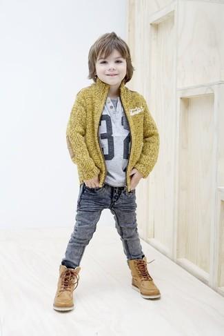Come indossare e abbinare: cardigan senape, t-shirt stampata grigia, jeans grigi, stivali in pelle marrone chiaro