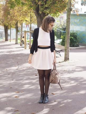 Come indossare: cardigan nero, top corto bianco, minigonna a pieghe bianca, stivaletti in pelle neri