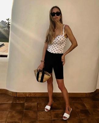 Come indossare e abbinare: corsetto a pois bianco e nero, pantaloncini ciclisti neri, sabot in pelle bianchi, borsa shopping di paglia marrone chiaro