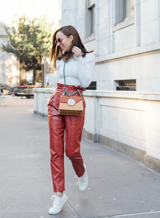 Come indossare e abbinare: dolcevita azzurro, pantaloni stretti in fondo in pelle rossi, sneakers basse in pelle bianche, borsa a tracolla in pelle terracotta