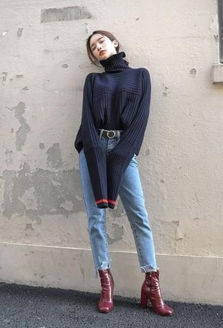 Come indossare e abbinare: dolcevita lavorato a maglia blu scuro, jeans azzurri, stivaletti in pelle bordeaux, cintura in pelle nera