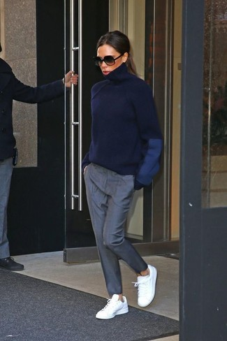 Come indossare e abbinare: dolcevita blu scuro, pantaloni stretti in fondo grigi, sneakers basse in pelle bianche