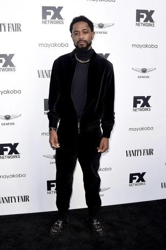 Come indossare e abbinare: dolcevita blu scuro, tuta sportiva di velluto nera, mocassini eleganti in pelle ricamati neri, orologio in pelle nero