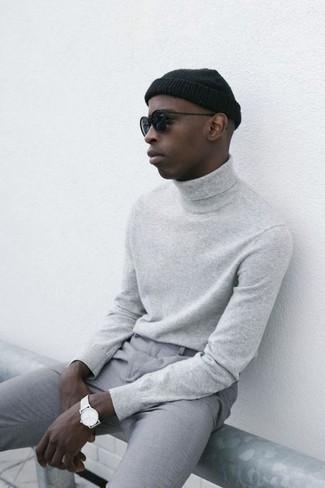 Come indossare: dolcevita grigio, chino grigi, berretto nera, occhiali da sole neri