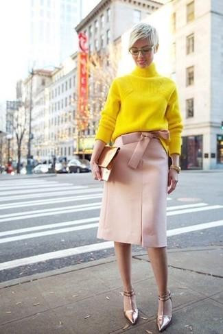 Come indossare: dolcevita lavorato a maglia giallo, gonna a tubino rosa, décolleté in pelle dorati, pochette in pelle dorata