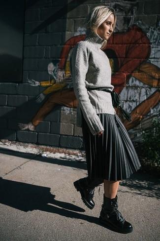 Come indossare e abbinare: dolcevita di lana grigio, gonna longuette a pieghe grigio scuro, stivali piatti stringati in pelle neri, marsupio in pelle verde scuro