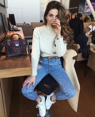 Come indossare e abbinare: dolcevita lavorato a maglia bianco, jeans aderenti blu, sneakers basse in pelle bianche, cartella in pelle melanzana scuro