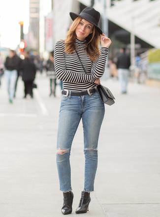 Trend da donna 2020: Vestiti con un dolcevita a righe orizzontali nero e bianco e jeans aderenti strappati azzurri per un look semplice, da indossare ogni giorno. Completa questo look con un paio di stivaletti in pelle neri.