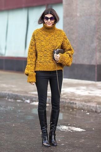 Come indossare e abbinare: dolcevita lavorato a maglia senape, jeans aderenti blu, stivali al ginocchio in pelle neri, pochette in pelle nera