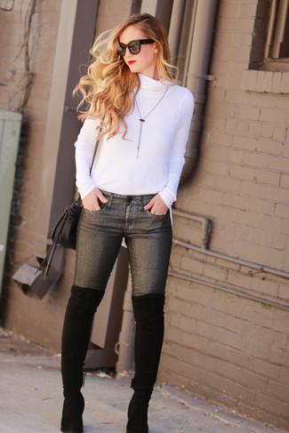 Come indossare: dolcevita bianco, jeans aderenti grigio scuro, stivali sopra il ginocchio in pelle scamosciata neri, borsa a tracolla in pelle nera