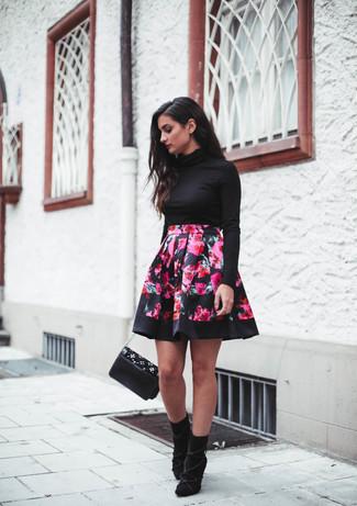 Come indossare e abbinare: dolcevita nero, gonna a pieghe a fiori fucsia, stivaletti in pelle scamosciata neri, borsa a tracolla in pelle decorata nera