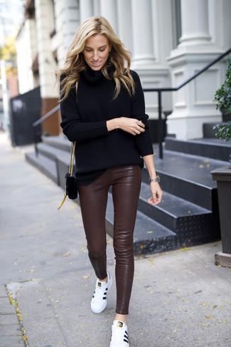 Come indossare: dolcevita nero, pantaloni skinny in pelle marrone scuro, sneakers basse in pelle bianche, borsa a tracolla in pelle scamosciata nera
