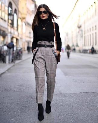 Come indossare e abbinare: dolcevita nero, pantaloni stretti in fondo a quadri marroni, stivaletti elasticizzati neri, cintura in pelle nera
