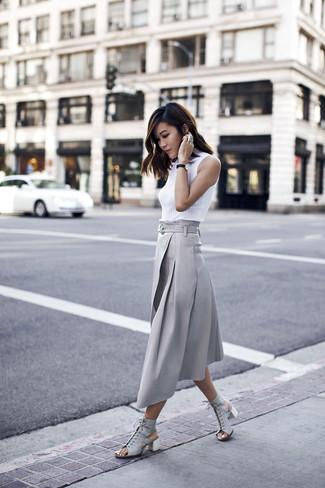 Come indossare: dolcevita senza maniche bianco, gonna longuette a pieghe grigia, sandali con tacco in pelle grigi
