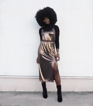 Come indossare: dolcevita nero, sottoveste di seta dorata, stivali al polpaccio in pelle scamosciata neri, orologio dorato