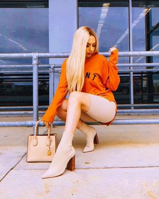 Come indossare e abbinare: felpa stampata arancione, pantaloncini ciclisti beige, stivaletti elasticizzati beige, borsa shopping in pelle beige