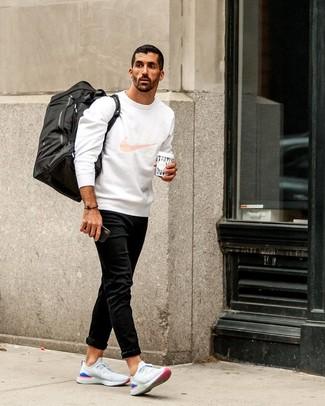 Come indossare e abbinare: felpa stampata bianca, jeans neri, scarpe sportive bianche, borsa per lo sport di tela nera