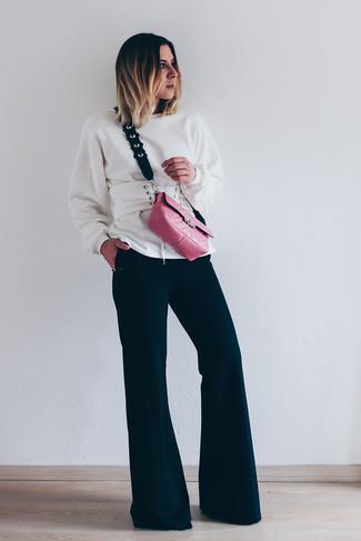 Come indossare e abbinare pantaloni a campana neri: Per un outfit quotidiano pieno di carattere e personalità, prova ad abbinare una felpa bianca con pantaloni a campana neri.