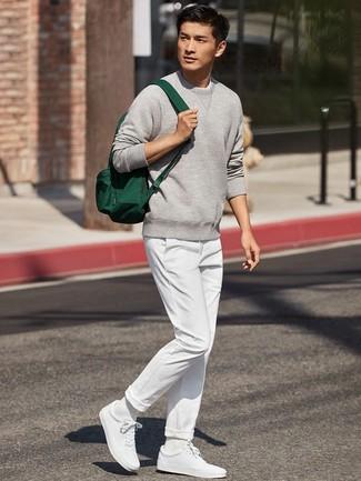 Come indossare e abbinare: felpa grigia, chino bianchi, sneakers basse bianche, zaino di tela verde scuro