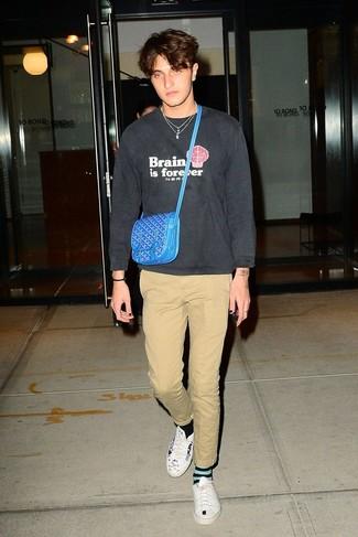 Moda ragazzo adolescente: Vestiti con una felpa stampata grigio scuro e chino marrone chiaro per un look spensierato e alla moda. Sneakers basse in pelle stampate bianche e nere sono una interessante scelta per completare il look.